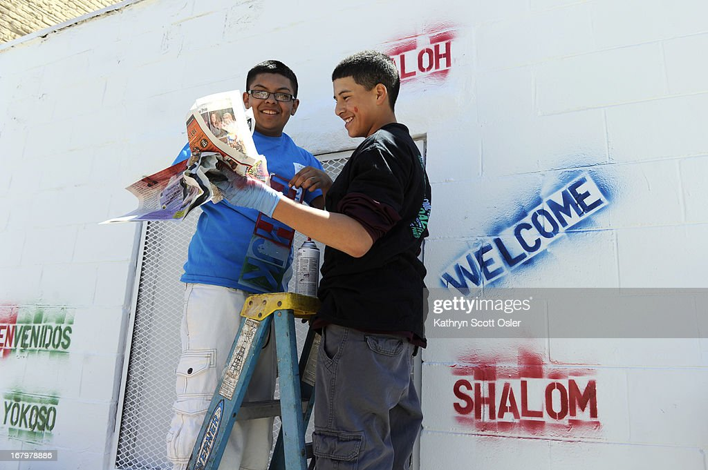 Miguel Gallegos, 15, left, and Larry Nolasco, 14, join a group of their ninth-grade classmates from Bruce Randolph School to perform a day of service in the Five Points neighborhood by painting multicultural murals to celebrate the diverse cultures of the Five Points community. The ninth-grade class was divided in to groups and participated in various service jobs in four different locations in Denver during the day.