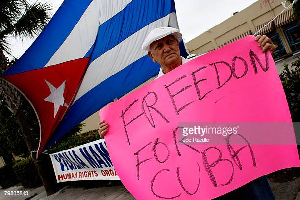 Miguel Gomez Beruvides holds a sign as he reacts to the news that Cuban President Fidel Castro announced he will not accept a new term in office in...