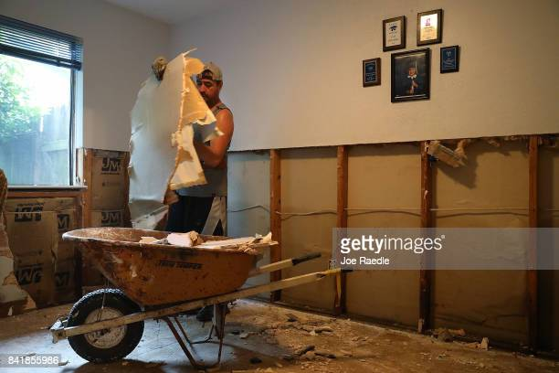 Miguel Gomez pulls sheetrock out of his home that was inundated with water as he begins the process of rebuilding after torrential rains caused...