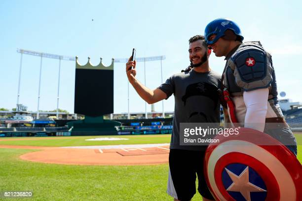 Miguel Gonzalez of the Chicago White Sox facetimes with his daughter and Captain America before the game against the Kansas City Royals at Kauffman...