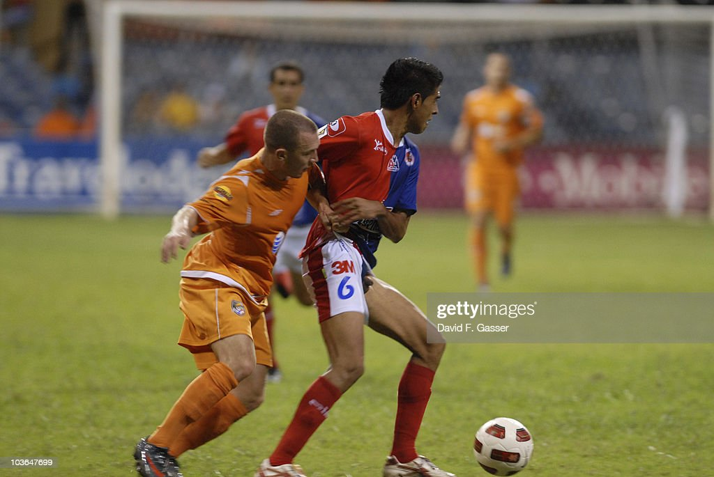 Miguel Granadino (R) of FAS vies the ball with David Foley of Islanders during their match as part of 2010 CONCACAg Champions League at Juan Ramon Loubriel Stadium on August 25, 2010 in Baymon, Puerto Rico.