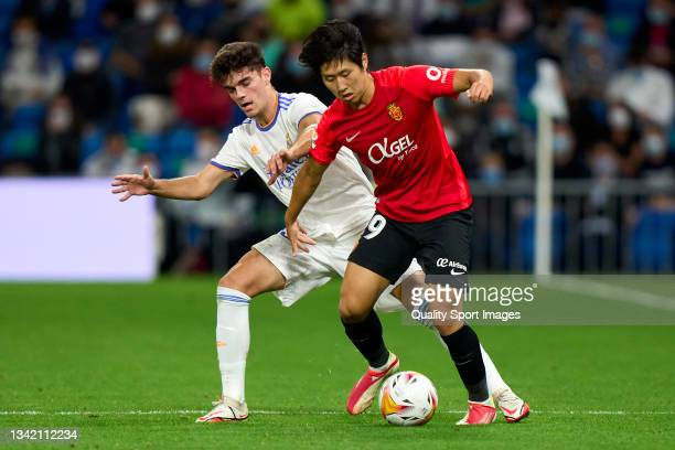 Miguel Gutierrez of Real Madrid CF battle for the ball with Kang-in Lee of RDC Mallorca during the La Liga Santander match between Real Madrid CF and...