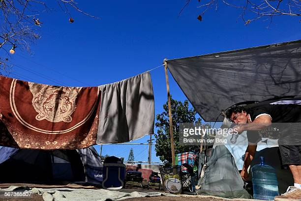January 17, 2015: Miguel Hernandez drinks water outside the tent where he lives along the Arroyo Seco and the Pasadena Freeway January 17, 2015 in...