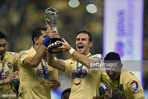 Miguel Layun and Jesus Molina of America hold the trophy after beating Tigres in their final match of Mexican Soccer Clausura 2014 tournament at the...