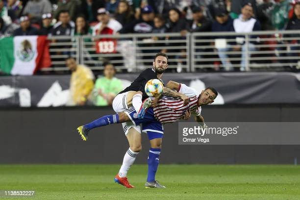 Miguel Layun of Mexico and Derlis Gonzalez fight the ball during the friendly match between Paraguay and Mexico at Levi's Stadium on March 26 2019 in...