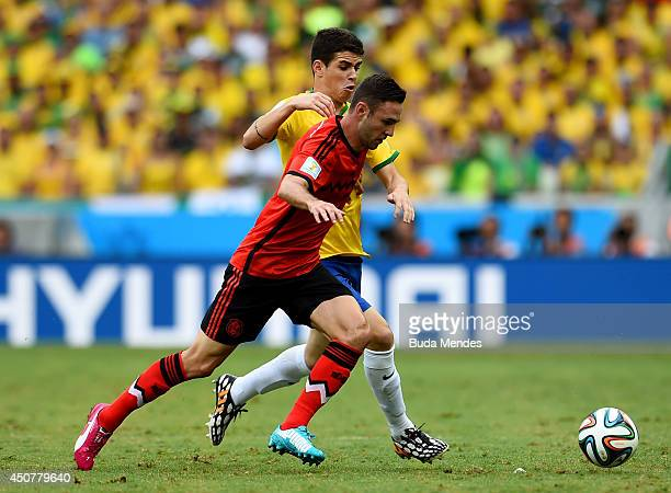 Miguel Layun of Mexico controls the ball against Alan Pulido of Mexico during the 2014 FIFA World Cup Brazil Group A match between Brazil and Mexico...