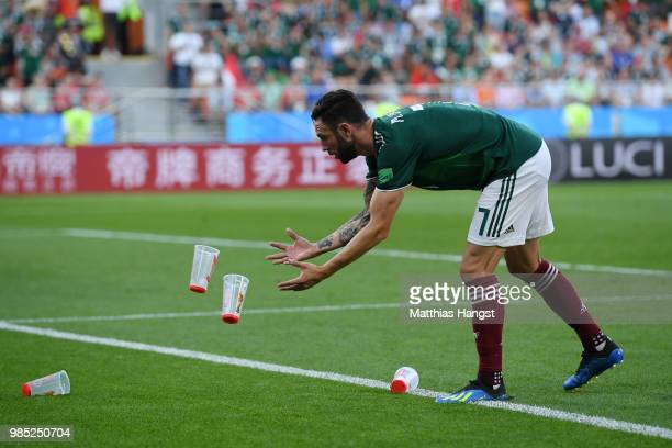 Miguel Layun of Mexico throws plastics cups of the pitch during the 2018 FIFA World Cup Russia group F match between Mexico and Sweden at...