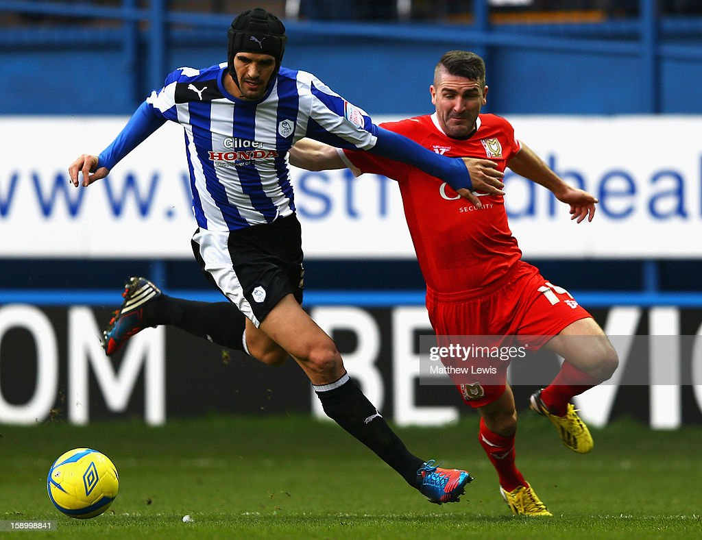 Miguel Llera of Sheffield holds off Ryan Lowe of Milton Keynes during the FA Cup with Budweiser Third Round match between Sheffield Wednesday and Milton Keynes Dons at Hillsborough Stadium on January 5, 2013 in Sheffield, England.