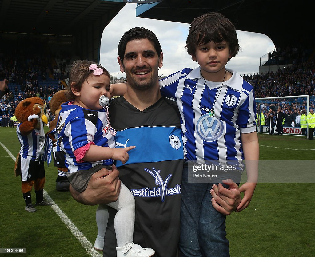 Miguel Llera of Sheffield Wednesday celebrates with his children as the players applaud the fans at the end of the npower Championship match between Sheffield Wednesday and Middlesbrough at Hillsborough Stadium on May 4, 2013 in Sheffield, England.