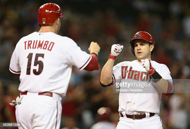 Miguel Montero of the Arizona Diamondbacks highfives Mark Trumbo after hitting a tworun home run against the San Diego Padres during the first inning...