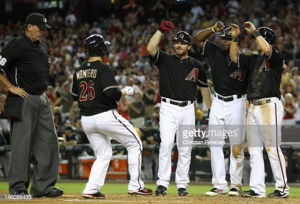 Miguel Montero of the Arizona Diamondbacks is congratulated at home plate by Jason Kubel Justin Upton and Willie Bloomquist after Montero hit a grand...