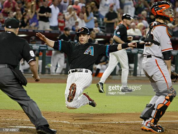 Miguel Montero of the Arizona Diamondbacks slides past catcher Buster Posey of the San Francisco Giants as he scores on the RBI single by teammate...