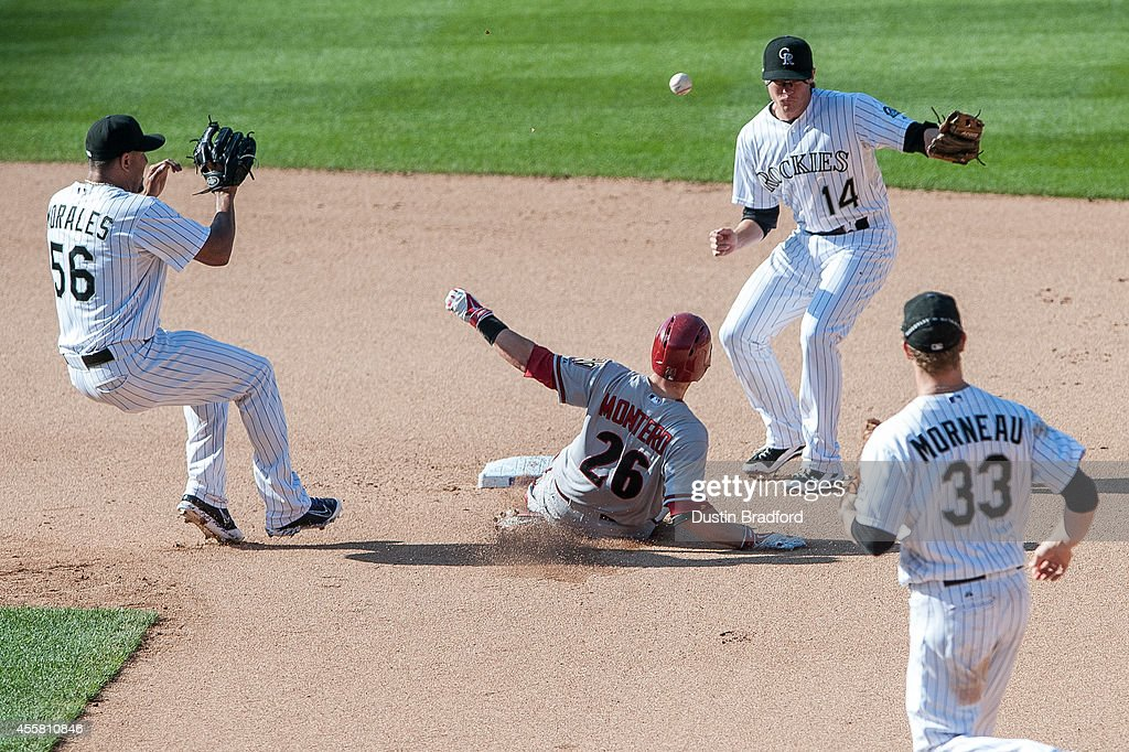Miguel Montero #26 of the Arizona Diamondbacks slides safely into second base with a seventh inning double as Franklin Morales #56, Josh Rutledge #14, and Justin Morneau #33 of the Colorado Rockies defend on the play during a game at Coors Field on September 20, 2014 in Denver, Colorado.