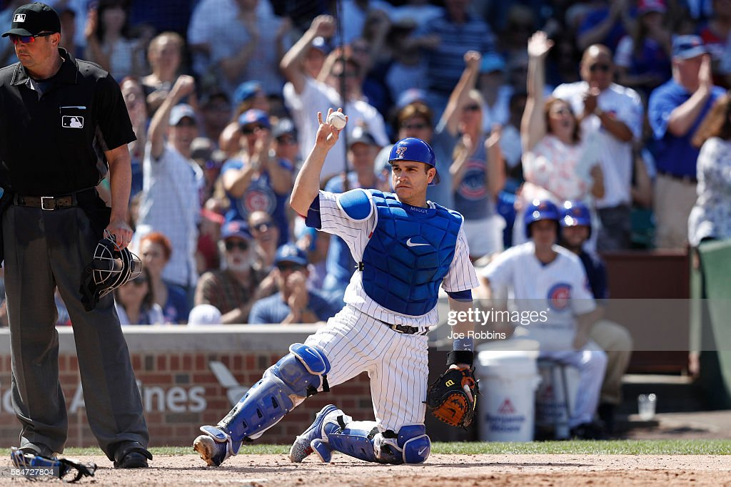 Miguel Montero #47 of the Chicago Cubs holds up the ball after tagging out Guillermo Heredia of the Seattle Mariners at home plate in the eighth inning at Wrigley Field on July 30, 2016 in Chicago, Illinois. The Mariners defeated the Cubs 4-1.