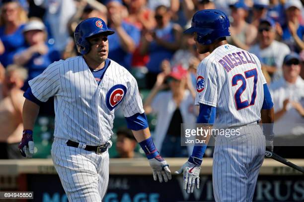 Miguel Montero of the Chicago Cubs is congratulated by Addison Russell after hitting a home run against the Colorado Rockies during the eighth inning...