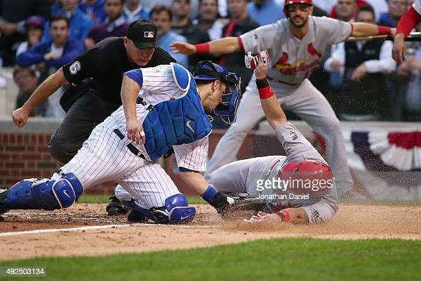 Miguel Montero of the Chicago Cubs tags out Tony Cruz of the St Louis Cardinals at home plate in the sixth inning during game four of the National...