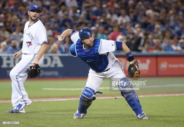 Miguel Montero of the Toronto Blue Jays fields a soft grounder and throws out the baserunner as Dominic Leone watches in the eighth inning during MLB...
