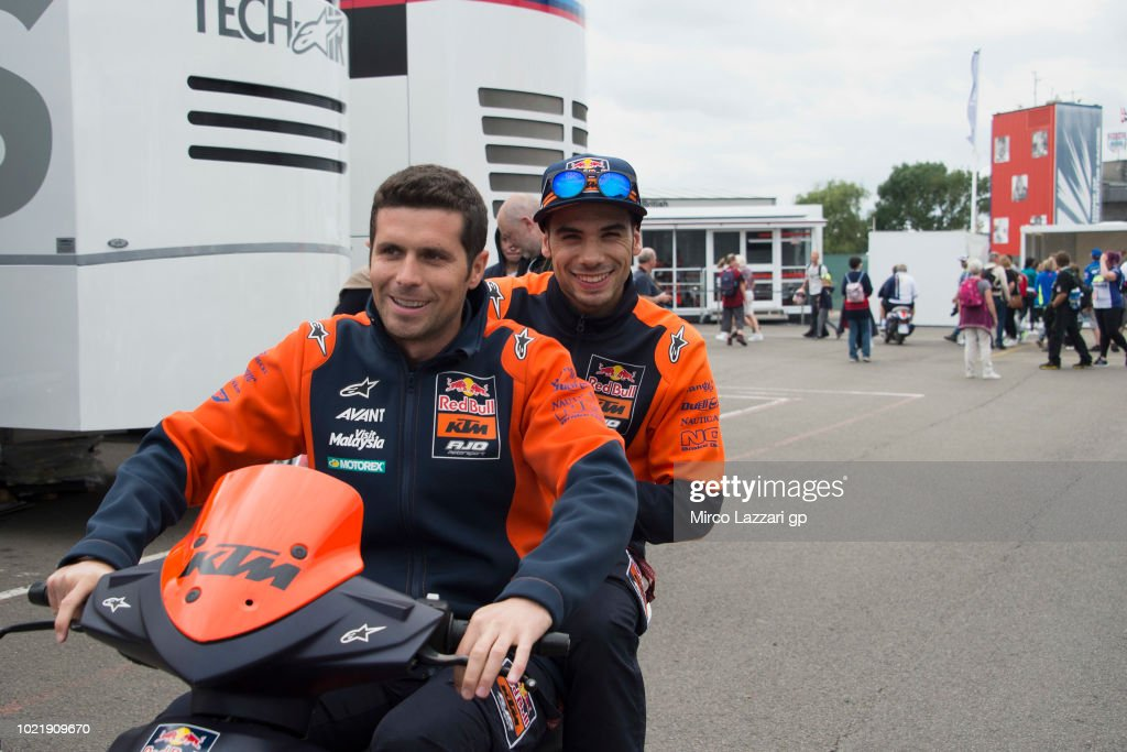 Miguel Oliveira of Portugal and Red Bull KTM Ajo (R) smiles in scooter in paddock during the MotoGp Of Great Britain - Previews at Silverstone Circuit on August 23, 2018 in Northampton, England.