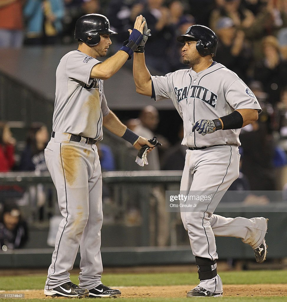 Miguel Olivo #30 (R) of the Seattle Mariners is congratulated by Dustin Ackley #13 after hitting a two-run homer against the Florida Marlins at Safeco Field on June 24, 2011 in Seattle, Washington. The Mariners defeated the Marlins 5-1.