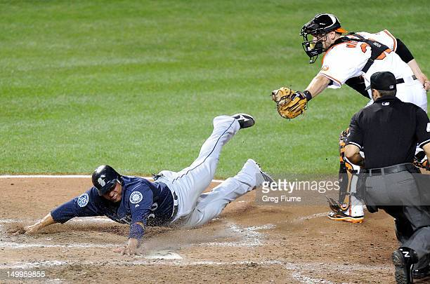 Miguel Olivo of the Seattle Mariners is tagged out at home plate by Matt Wieters of the Baltimore Orioles at Oriole Park at Camden Yards on August 7...