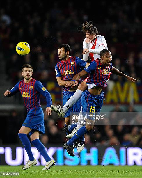 Miguel Perez 'Michu' of Rayo Vallecano duels for a high ball with Javier Mascherano of FC Barcelona and Seydou Keita of FC Barcelona during the La...