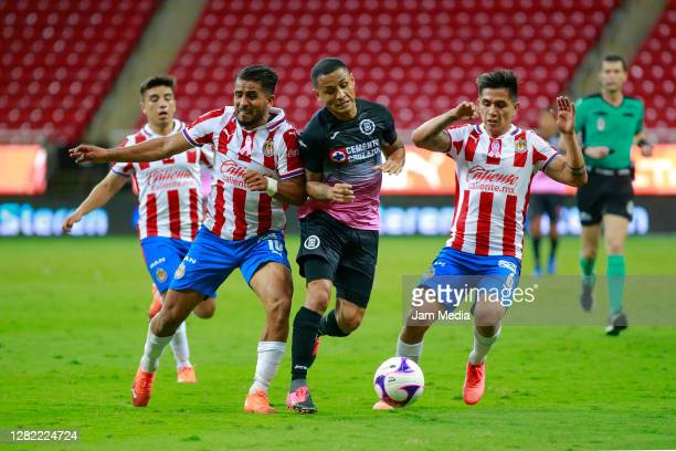 Miguel Ponce and Fernando Beltran of Chivas fight for the ball with Victor Yoshimar Yotun of Cruz Azul during the 15th round match between Chivas and...