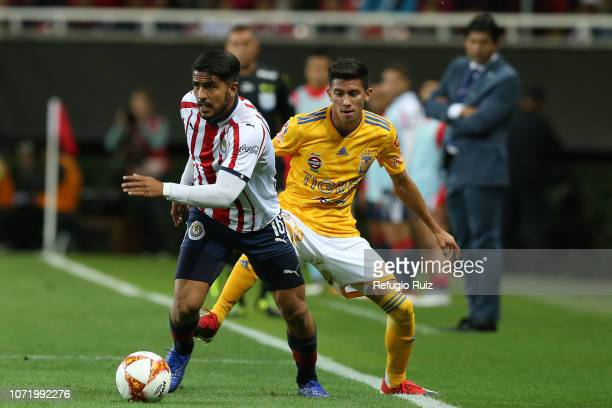 Miguel Ponce of Chivas fights for the ball with Raul Torres of Tigres during the 17th round match between Chivas and Tigres as part of the Torneo...