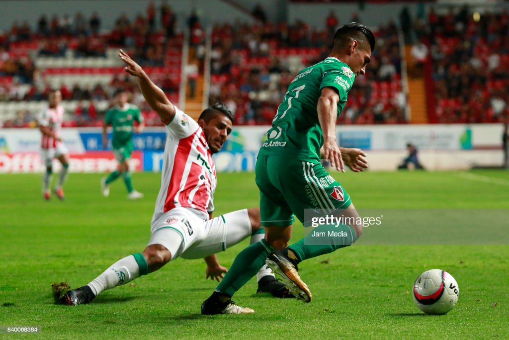 Miguel Ponce of Necaxa slides for the ball agianst Jose Maduena of Atlas during the seventh round match between Necaxa and Atlas as part of the Torneo Apertura 2017 Liga MX at Victoria Stadium on August 26, 2017 in Aguascalientes, Mexico.