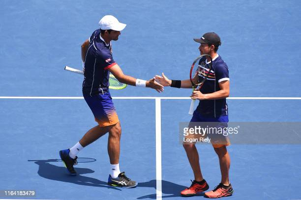 Miguel Reyes-Varela of Mexico high fives his teammate Marcelo Arevalo of El Salvador after a point against Radu Albot of Moldova and Artem Sitak of...