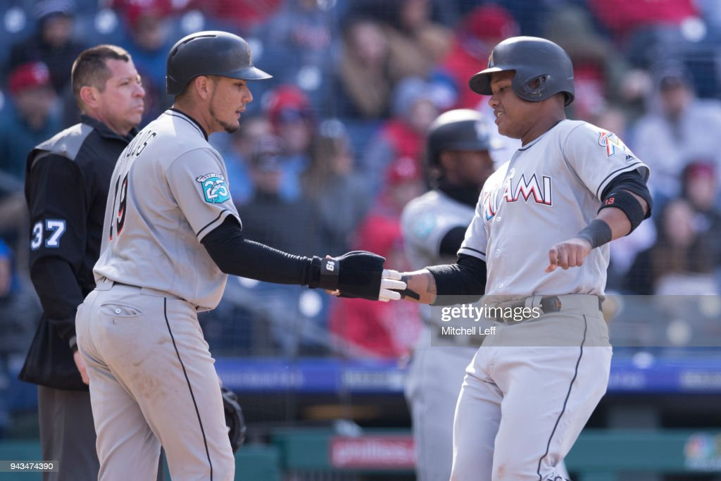 Miguel Rojas #19 and Starlin Castro #13 of the Miami Marlins celebrate after both scoring a run in the top of the eighth inning against the Philadelphia Phillies at Citizens Bank Park on April 8, 2018 in Philadelphia, Pennsylvania. The Marlins defeated the Phillies 6-3.