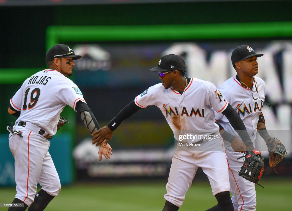 Miguel Rojas #19, Cameron Maybin #1, and Starlin Castro #13 of the Miami Marlins celebrate the win at the end of the game after beating the Colorado Rockies at Marlins Park on April 29, 2018 in Miami, Florida.