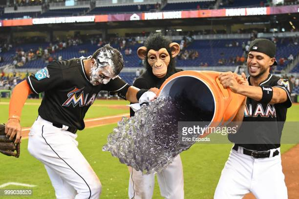 Miguel Rojas of the Miami Marlins and Yadiel Rivera attempt to pour gatorade on Martin Prado after defeating the Philadelphia Phillies at Marlins...