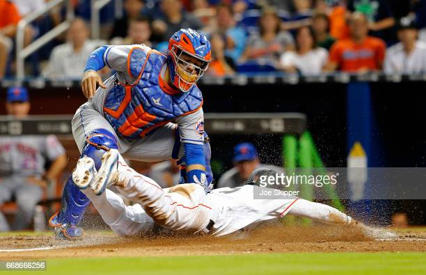Miguel Rojas of the Miami Marlins is tagged out at home in the eighth inning by Rene Rivera of the New York Mets at Marlins Park on April 14 2017 in...