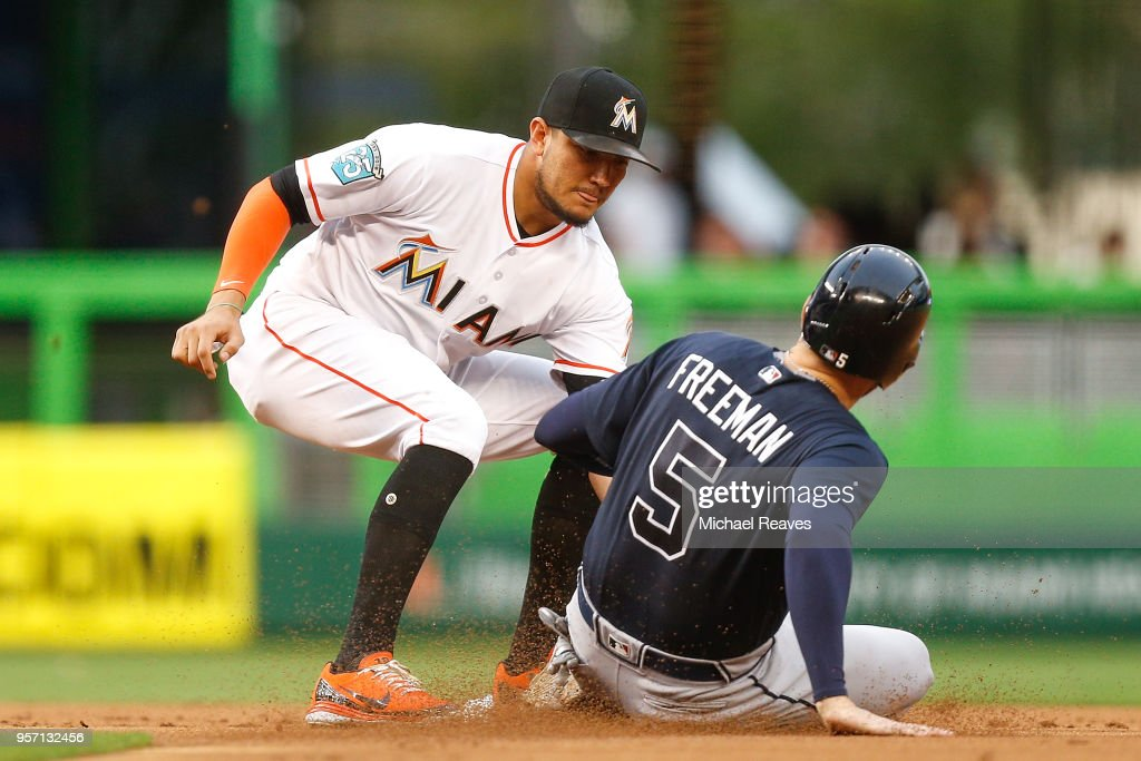 Miguel Rojas #19 of the Miami Marlins tags out Freddie Freeman #5 of the Atlanta Braves after he was picked off during the first inning at Marlins Park on May 10, 2018 in Miami, Florida.