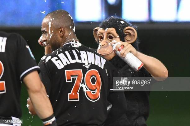 Miguel Rojas of the Miami Marlins wearing a monkey mask puts whip cream on Isaac Galloway after he hit a walkoff single in the tenth inning against...