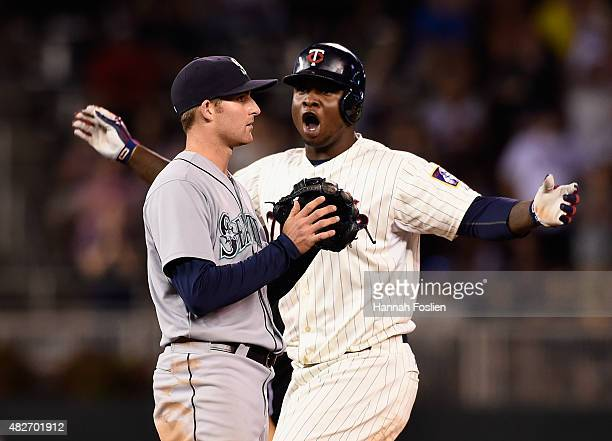Miguel Sano of the Minnesota Twins celebrates a leadoff double as Brad Miller of the Seattle Mariners looks on during the ninth inning of the game on...