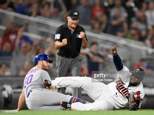 Miguel Sano of the Minnesota Twins celebrates as umpire Tim Timmons calls Pete Alonso of the New York Mets out at third base to complete a double...