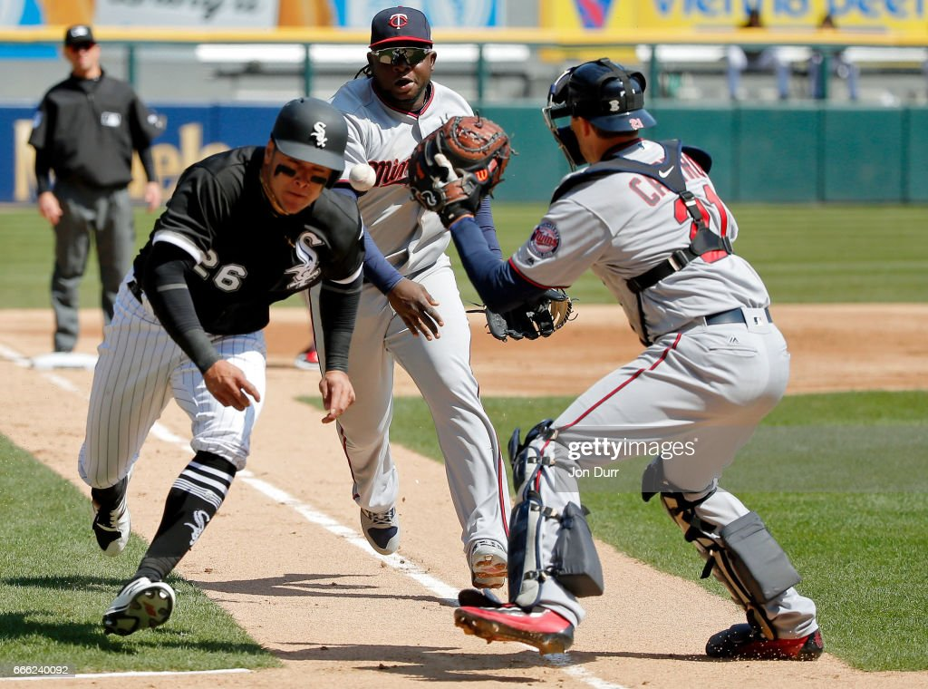 Miguel Sano #22 of the Minnesota Twins commits a throwing error as Avisail Garcia #26 of the Chicago White Sox is able to safely steal home on a pick off attempt during the second inning at Guaranteed Rate Field on April 8, 2017 in Chicago, Illinois.