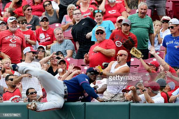 Miguel Sano of the Minnesota Twins falls into the netting while attempting to catch a foul ball hit by Eugenio Suarez of the Cincinnati Reds in the...