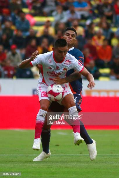 Miguel Sansores of Morelia fights for the ball with Anderson Santamaria of Puebla during the 13th round match between Morelia and Puebla as part of...