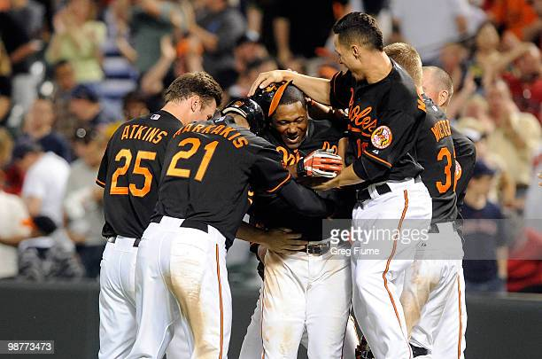 Miguel Tejada of the Baltimore Orioles is mobbed by teammates after driving in the game winning run in the tenth inning against the Boston Red Sox at...