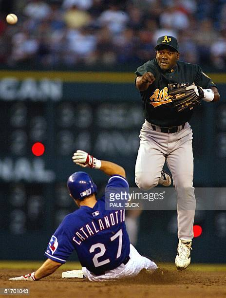 Miguel Tejada of the Oakland Athletics forces Texas Ranger Frank Catalanotto out at second base and then completes the double play in the second...