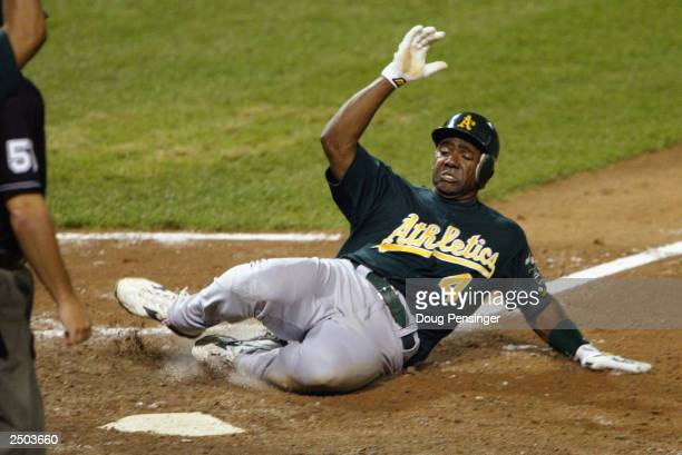 Miguel Tejada of the Oakland Athletics slides to score the eventual winning run on a sacrifice fly by teammate Mark Ellis in the top of the 12th...