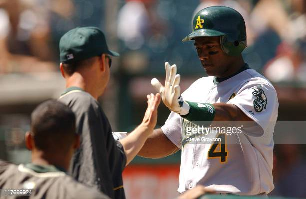 Miguel Tejeda of the A's is greeted in the dugout after scoing on a Scott Hatteberg double in the second inning