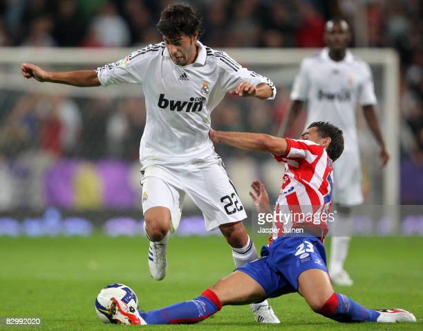 Miguel Torres of Real Madrid duels for the ball with David Barral of Real Sporting de Gijon during the La Liga match between Real Madrid and Real...