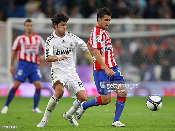 Miguel Torres of Real Madrid duels for the ball with Francisco Maldonado of Real Sporting de Gijon during the La Liga match between Real Madrid and...