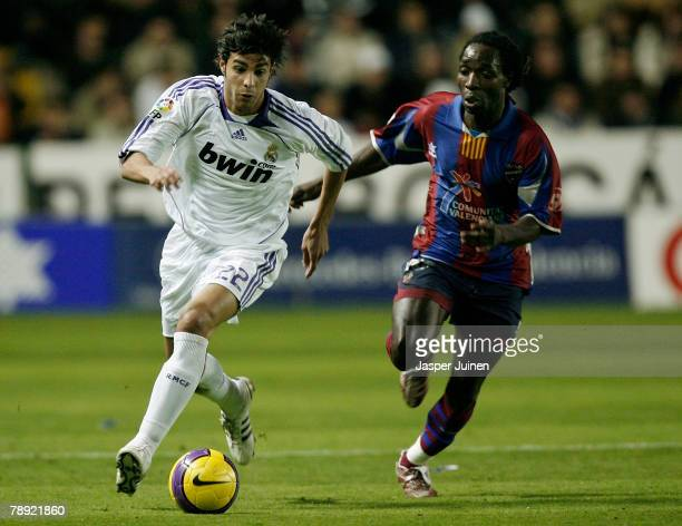 Miguel Torres of Real Madrid duels for the ball with Mustapha Riga of Levante during the La Liga match between Levante and Real Madrid at the Ciutat...