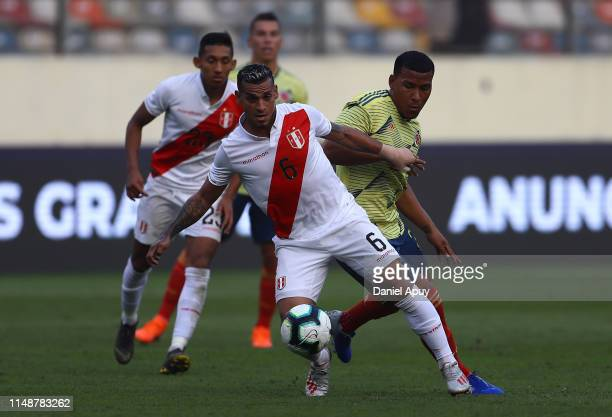 Miguel Trauco of Peru and Roger Martinez of Colombia compete for the ball during a friendly match between Peru and Colombia at Estadio Monumental on...