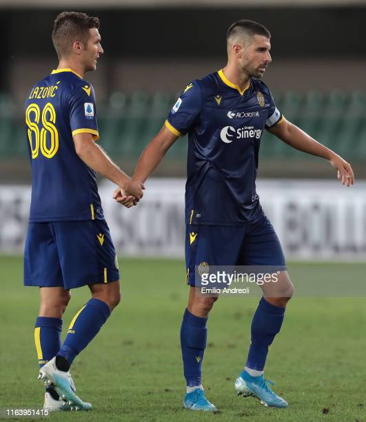 Miguel Veloso of Hellas Verona celebrates with his teammate Darko Lazovic at the end of the Serie A match between Hellas Verona and Bologna FC at...