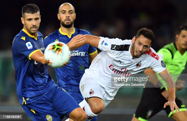Miguel Veloso of Hellas Verona competes for the ball with Hakan Calhanoglu of AC Milan during the Serie A match between Hellas Verona and AC Milan at...